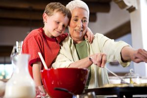 Caucasian grandmother and grandson cooking together