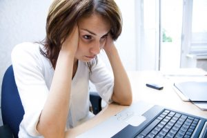 young businesswoman thought for laptop holding hands her head